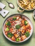 健康平衡的膳食 有鸡的平底锅在西红柿酱、绿色硬花甘蓝和被烘烤的土豆编结 库存图片