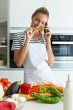 健康年轻女人吃新鲜蔬菜片断和在家谈话与她的手机在厨房里 库存照片