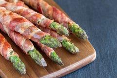 健康开胃菜,绿色芦笋包裹用在木的烟肉 图库摄影