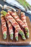 健康开胃菜,绿色芦笋包裹用在木的烟肉 免版税库存图片