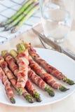 健康开胃菜,绿色芦笋包裹用在白色的烟肉 免版税库存照片