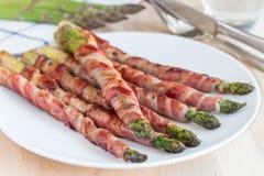 健康开胃菜,绿色芦笋包裹用在白色p的烟肉 免版税库存照片