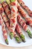 健康开胃菜,绿色芦笋包裹用在白色p的烟肉 库存照片