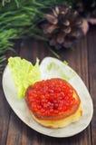 健康开胃菜:三明治用在白色瓷板材的红色鱼子酱 木背景 顶视图 特写镜头 免版税图库摄影