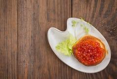 健康开胃菜:三明治用在白色瓷板材的红色鱼子酱 木背景 顶视图 特写镜头 图库摄影
