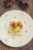 健康开胃菜:与海三文鱼和红色鱼子酱的三明治在白色瓷板材 木背景 顶视图 库存图片