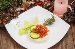 健康开胃菜:与海三文鱼和红色鱼子酱的三明治在白色瓷板材 木背景 顶视图 免版税库存图片