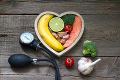 健康心脏饮食与血压测量仪的食物概念 免版税库存图片