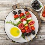 健康快餐:在一顿野餐用蕃茄,无盐干酪,蒜味咸腊肠,黑橄榄,蓬蒿,意大利式饺子的味道好的kebabs 免版税库存照片