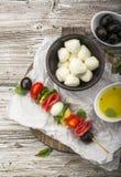 健康快餐:在一顿野餐用蕃茄,无盐干酪,蒜味咸腊肠,黑橄榄,蓬蒿,意大利式饺子的味道好的kebabs 免版税图库摄影