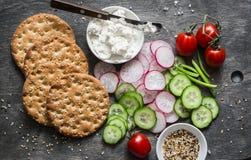 健康快餐-整个五谷薄脆饼干、黄瓜、蕃茄、萝卜和乳酪在木背景,顶视图 库存图片