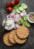 健康快餐-整个五谷薄脆饼干、黄瓜、蕃茄、萝卜和乳酪在木背景 库存图片