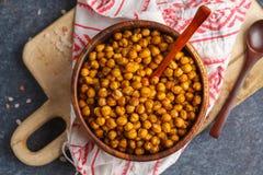 健康快餐-在一个木碗,顶视图的被烘烤的辣鸡豆 免版税图库摄影