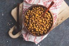 健康快餐-在一个木碗,顶视图的被烘烤的辣鸡豆 免版税库存图片