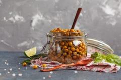 健康快餐-在一个玻璃瓶子的被烘烤的辣鸡豆 健康ve 免版税库存图片