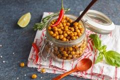 健康快餐-在一个玻璃瓶子的被烘烤的辣鸡豆 健康ve 免版税库存照片