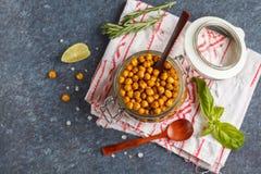 健康快餐-在一个玻璃瓶子,顶视图的被烘烤的辣鸡豆, 库存照片