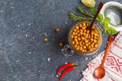 健康快餐-在一个玻璃瓶子,顶视图的被烘烤的辣鸡豆, 免版税库存图片