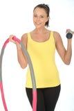 健康愉快的拿着一个沉默寡言的响铃和健身Hula箍的适合少妇 免版税库存照片