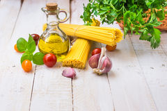 健康意大利样式膳食的成份与意粉,蕃茄,蓬蒿,大蒜,荷兰芹,在板条木厨房用桌上的橄榄油 库存照片