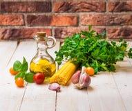 健康意大利膳食的成份与意粉,蕃茄,蓬蒿,大蒜,荷兰芹,橄榄油 免版税库存图片