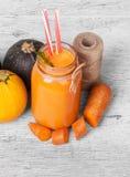 健康成份的美好的构成和螺纹卷在灰色背景的 一个巨大的瓶子红萝卜汁 免版税库存图片