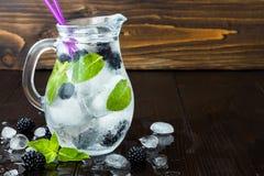 健康戒毒所调味了水用黑莓和薄菏 与冰的冷的刷新的莓果饮料在黑暗的木桌上 复制空间backg 免版税库存照片