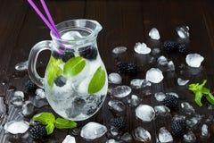 健康戒毒所调味了水用黑莓和薄菏 与冰的冷的刷新的莓果饮料在黑暗的木桌上 复制空间backg 库存图片