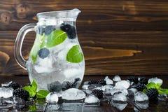 健康戒毒所调味了水用黑莓和薄菏 与冰的冷的刷新的莓果饮料在黑暗的木桌上 复制空间backg 免版税图库摄影