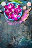 健康或温泉背景与桃红色兰花在碗开花有海盐水、铁锹,奶油色瓶子、蜡烛和绿色竹子的 免版税库存图片