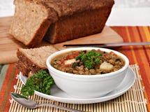 健康扁豆,菠菜汤用奎奴亚藜面包。 库存照片