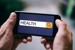 健康技术概念-在查寻酒吧写的健康在流动屏幕或智能手机显示 免版税库存照片