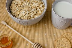 健康整粒早餐:燕麦粥、牛奶、饼干、蜂蜜和花瓶有玫瑰的 图库摄影