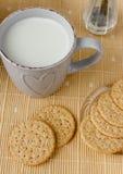 健康整粒早餐:燕麦粥、牛奶、饼干、蜂蜜和花瓶有玫瑰的 库存照片
