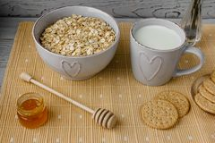 健康整粒早餐:燕麦粥、牛奶、饼干、蜂蜜和花瓶有玫瑰的 免版税库存照片