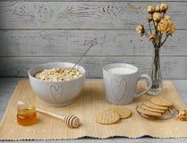 健康整粒早餐:燕麦粥、牛奶、饼干、蜂蜜和花瓶有玫瑰的 免版税图库摄影