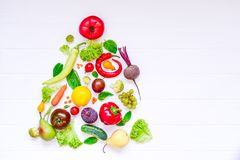 健康新年概念-新鲜的有机蔬菜、草本和水果以圣诞树的形式在白色木背景 二 免版税库存照片