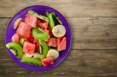 健康新鲜水果沙拉板材在木背景的 图库摄影