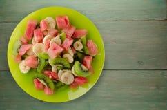 健康新鲜水果沙拉板材在木背景的 免版税库存图片