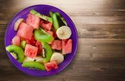 健康新鲜水果沙拉板材在木背景的 库存照片