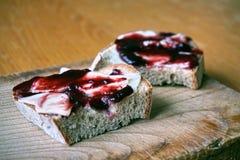 健康早晨早餐由果酱制成在白面包,投入了葡萄酒木砧板 图库摄影