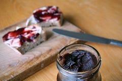 健康早晨早餐由果酱制成在白面包,投入了葡萄酒木砧板 免版税库存照片