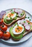 健康早餐、多士用鲕梨,鸡蛋、萝卜、甜葱和蕃茄,饮食食物,在轻的大理石背景,有选择性 免版税库存照片