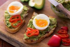 健康早餐三明治准备了与鳄梨调味酱捣碎的鳄梨酱,胡椒并且煮沸了在木黑板的鸡鸡蛋 免版税库存图片