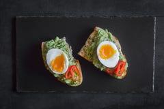 健康早餐三明治准备了与鳄梨调味酱捣碎的鳄梨酱,胡椒并且煮沸了鸡鸡蛋 免版税库存照片