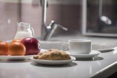 健康早餐在厨房里用咖啡、新月形面包、牛奶和果子 免版税库存图片