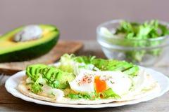 健康早餐想法 可口玉米粉薄烙饼用一个荷包蛋、鳄梨片、napa圆白菜、沙拉混合、调味汁和香料 免版税库存照片