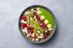 健康早餐戒毒所绿色圆滑的人用香蕉和菠菜在碗,顶视图 免版税库存照片