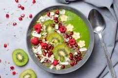 健康早餐戒毒所绿色圆滑的人用香蕉和菠菜在碗,顶视图 免版税库存图片