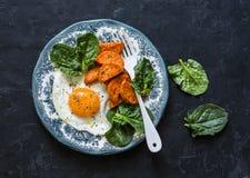 健康早餐或快餐-煎蛋、被烘烤的白薯和菠菜在黑暗的背景,顶视图 免版税库存图片